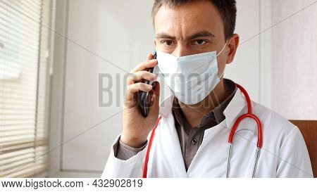 Worried Doctor With A Surgical Mask On The Face Is Talking On Phone Receiving News