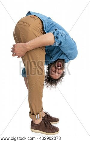 side view of a casual man leaning forward and holding his legs against white background