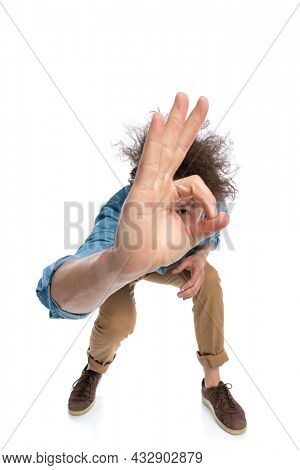 young casual man leaning forward and peeking through the finger hole on white background