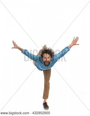 handsome casual man leaning forward and standing on one leg only on white background