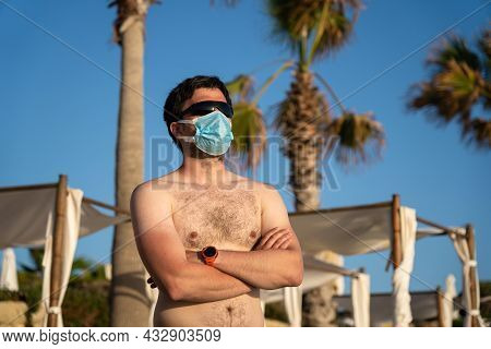 Man In Medical Mask Stands Alone On Empty Beach Near Sun Loungers And Palm Trees On Cyprus, Paphos C
