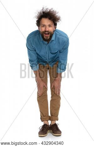 casual young man leaning forward and feeling surprised against white background