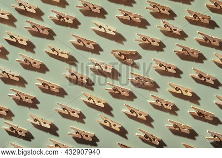 Pattern with  repeated old clothespins on light green background. One clothespin is opened. Beautiful household design elements. Concept: one against the system