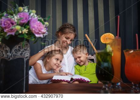 Mom and children are reading a book. Pretty young mother and lovely kids having fun in lounge room witth cocktails