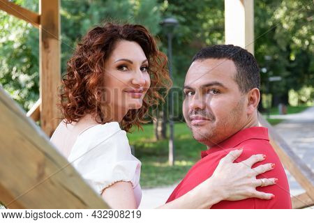 Loving Couple On Park Bench Turned Around And Looked At The Camera. Man In Red T-shirt And A Curly W