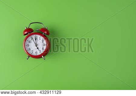 Red Alarm Clock On Green Color Background. Red Alarm Clock Images Placed On A Green Background, Time