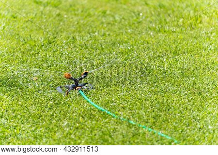 View Of Automatic Irrigation Of A Lawn With Green Grass On A Sunny Day Using Mobile Equipment For Ir