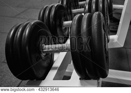 Heavy Dumbbells In The Gym. Sports Dumbbells In In A Rack In Sports Club. Black And White Photo