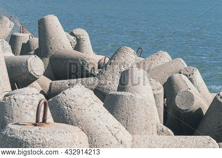 Concrete Tetrapod Breakwaters Lie All Along The Coast. Coast Breakwaters Protecting From Large Waves
