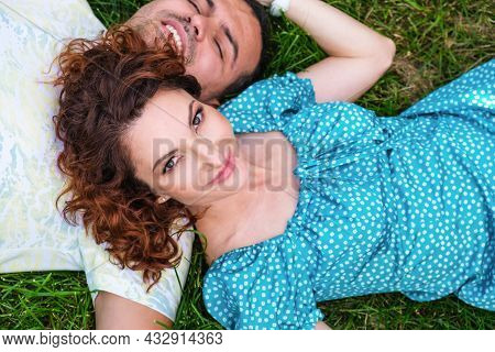 Attractive Woman With Red Hair In Blue Dress And Young Man Lie On The Grass. Wife Lies On Her Husban