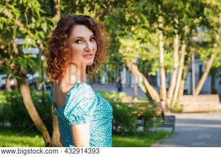 Attractive Young Woman With Red Hair In A Blue Dress Turned Around And Looked At The Camera. Beautif
