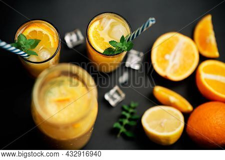 Delicious Fresh Orange Juice With Ice, Mint And Fresh Fruits On Black Table Background