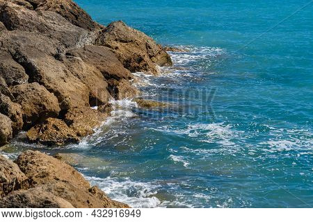 Waves Of The Mediterranean Sea On A Rocky Coast In Cyprus Near The City Of Paphos In Sunny Summer We