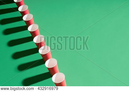 Row Of Red Paper Cup On Green Background With Copy Space