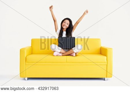 Happy Smiling Woman With Raised Arms Sitting On Yellow Couch With Laptop