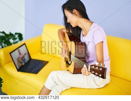 Smiling Pretty Female Learning To Play Guitar Watches A Video Lesson Online Using Laptop