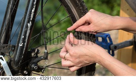 Women's Hands Between The Spokes On The Rim Of The Wheel. Bicycle Repair Concept.