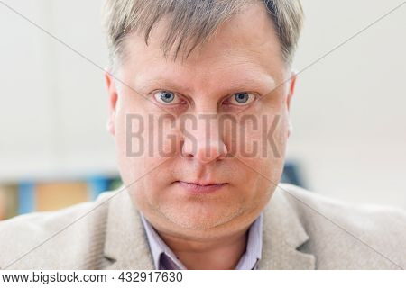 An Adult Male Professor In A Jacket With A Serious Look Looks Straight At Him.