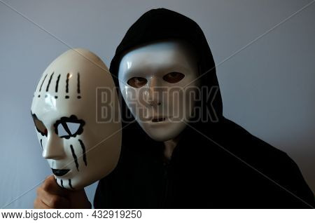 Man With Black Hood Wearing An Anonymous White Mask And Holding A Female White Mask On Grey Backgrou