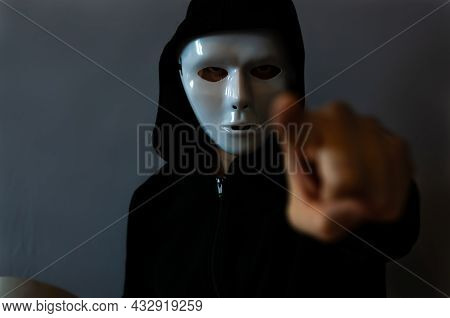 Man With A Black Hooded Jacket Wearing A Halloween White Mask And With A Pointing Finger, On Dark Ba