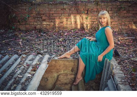 Young Woman With Bob Haircut In A Turquoise Evening Dress On One Shoulder Is Sitting On The Edge Of