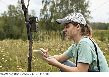 Young Woman Scientist Zoologist Writing Down Data From Trap Camera To Notepad, Observing Wild Animal