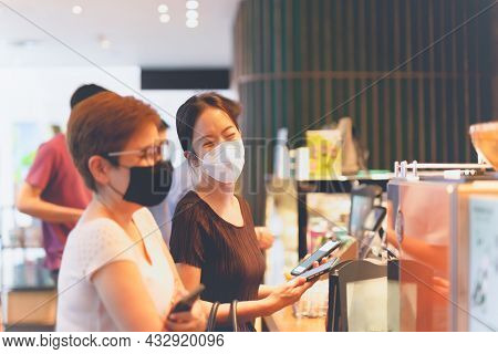 Two Happy Female Friends In Protective Mask Buying Coffee