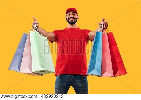 Middle-eastern Male Courier Giving Shopper Bags Delivering Clothes, Yellow Background