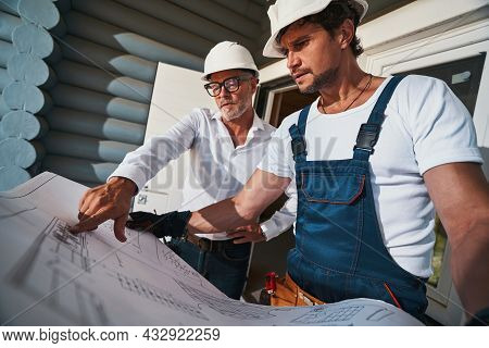 Civil Engineer Showing Place In Blueprint To Worker