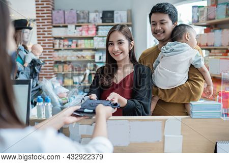 Family Making A Payment At The Baby Shop Using Credit Card At The Cashier