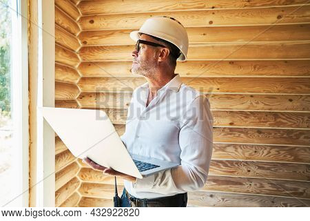 Civil Engineer In Safety Cap Working With Laptop In Building