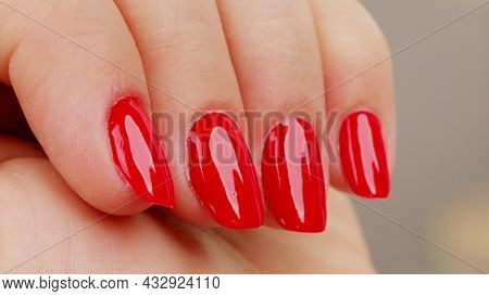 Female hands with fashionable manicure of red color . Woman shows her new red manicured nails, closeup. Beauty of nails. Classic red manicure.