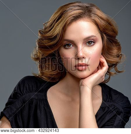 Beautiful brown haired with stylish short hairstyle. Woman with a  curly hair. Beautiful young woman with freckles on face.  Closeup portrait of an attractive girl  with a brown makeup.
