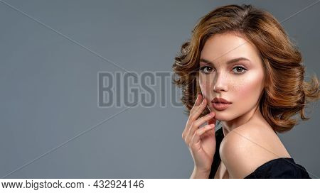Woman with a  curly hair. Beautiful young woman with freckles on face.   Beautiful brown haired with stylish short hairstyle.  Closeup portrait of an attractive girl  with a brown makeup.