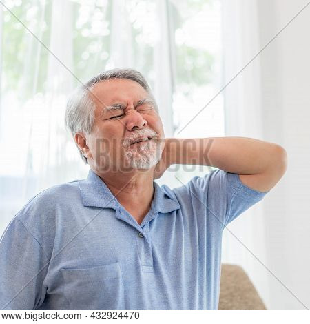 Senior Asian Man , Old Man He Wake Up And Sat On Sofa , He Had Pain In The Nape Of His Neck Caused B