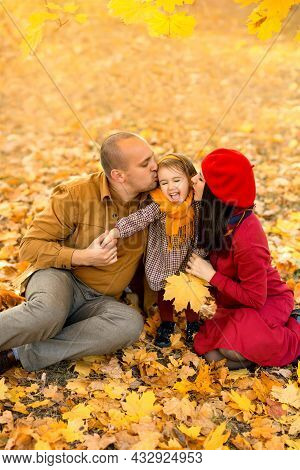 A Mother And Father Kiss Their Two-year-old Daughter On The Cheek, Sitting On The Dry Yellow Leaves