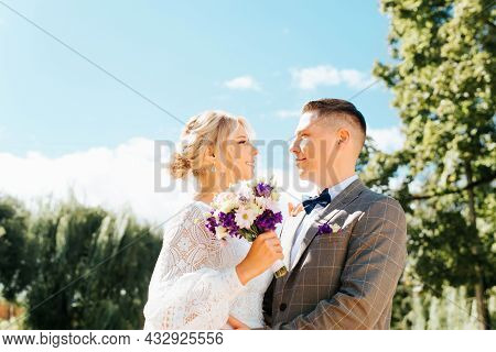 Profile Portrait Of Happy Young Married Couple, Beautiful Smiling Bride With Bouquet And Groom Look