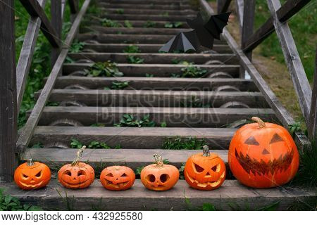 There Are Jack - O ' - Lantern Pumpkins With Different Emotions Carved On The Old Wooden Steps In A