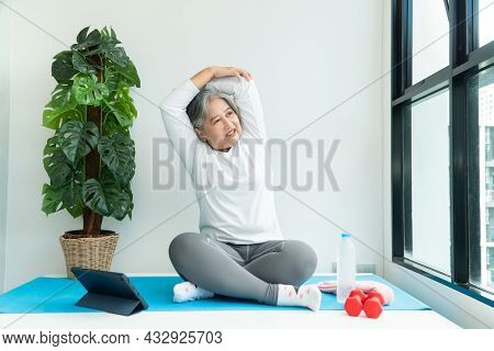 Senior Asian Woman Watching Online Courses On A Laptop While Exercising In The Living Room At Home.
