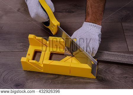 A Man Cuts The Skirting Board Using A Saw And Miter Box On Laminate Floor.
