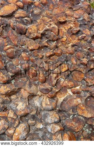 Background Texture Of Surface Of Rock Made Of Brown Rounded Stones. Vertical Image.