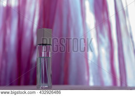 A Long Perfume Bottle Stands Against A Blurred Pink Fabric. Glass Vial With A Metal Cap. Blank For M