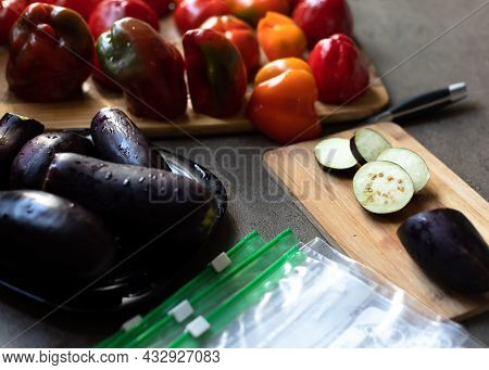 A Woman Cuts Red Peppers And Eggplants Into Pieces And Puts Them In Plastic Freezer Bags. Freezing V