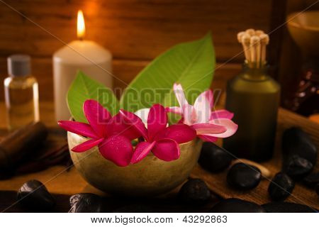 Spa setting with frangipani flower, essential oil, zen stones and aromatic candles on table, Zen concept.