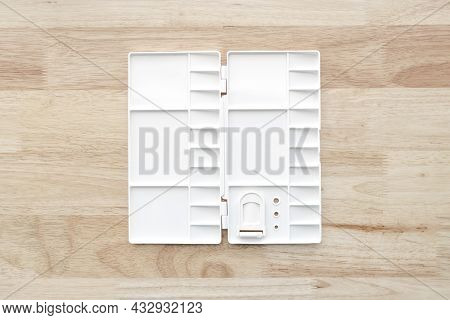 White Watercolor Palette. Empty Watercolor Tray Isolated On Wood Background. White Plastic Paint Pal