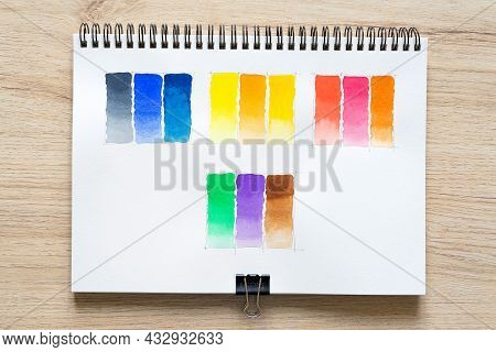 Watercolor Paint On White Notebook Paper With Wood Background. Colorful Shade Collection On White Pa