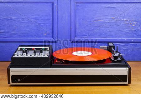 Vintage Turntable Vinyl Record Player With Red Vinyl On Table By Blue Wall.