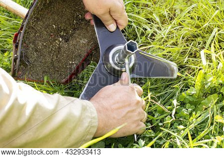 Farmer Or Worker Unscrews Grass Or Lawn Trimmer Knives Against Green Grass Background