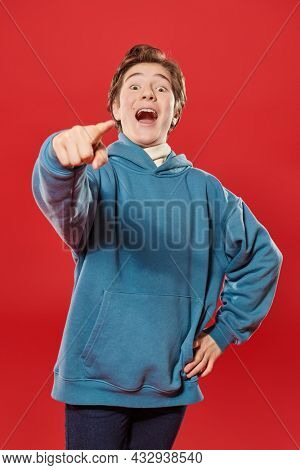 Emotional boy teenager points his finger at the camera and laughs out loud. Teenage emotions and relationships. Education. Studio portrait on a red background.