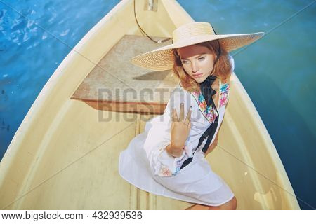 An elegant blonde girl in a white summer dress and a wide-brimmed straw hat rides a boat on the sea. Sea resort, summer vacation. Beauty, fashion.